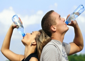A man and woman drinking water.