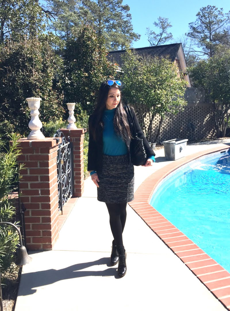 Outside wearing black texttured sweater jacket, ocean blue turtleneck, black and white tweed skirt, black tights, black booties, and blue mirrored sunglasses on head.