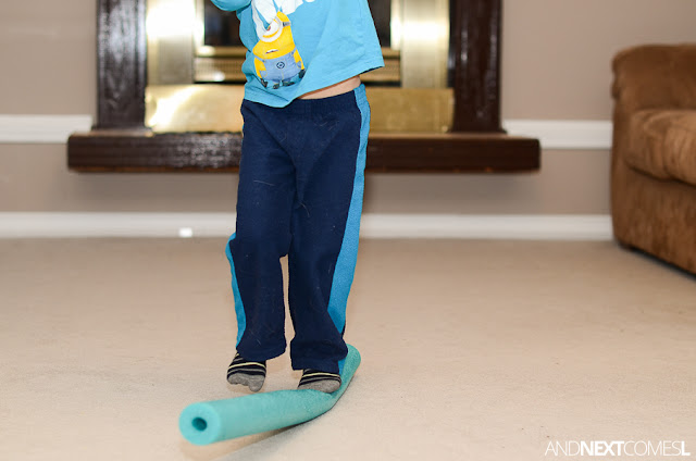 For a quick vestibular gross motor activity for kids, set up this simple DIY balance beam using a pool noodle from And Next Comes L
