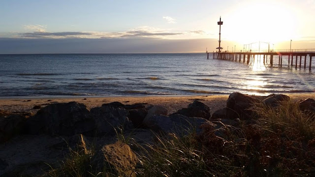 View from the shore of Brighton Jetty and beach with the sun setting on the horizon. In the foreground is a rock wall.