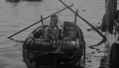 Em chèo xuồng bán quán trên sông