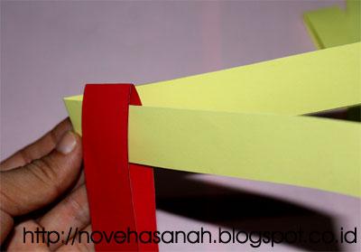 langkah pembuatan ikan perhias dari kertas bekas adalah dengan menganyam pita-pita kertas. Pertama-tama kaitkan 2 pita kertas dengan warna yang berbeda