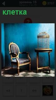 Около стены стул и стол, на котором помещена пустая клетка, которая освещена теплым светом