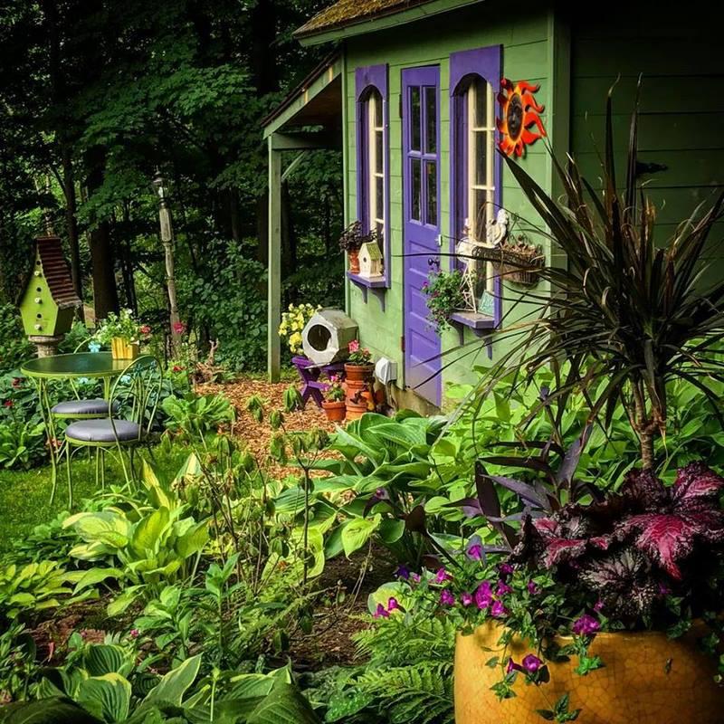 casa con jardín pintada en verde y morado, mesas en verde y macetas en amarillo