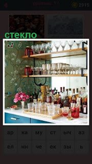 на полках стоит посуда сделанная из стекла, стаканы, фужеры