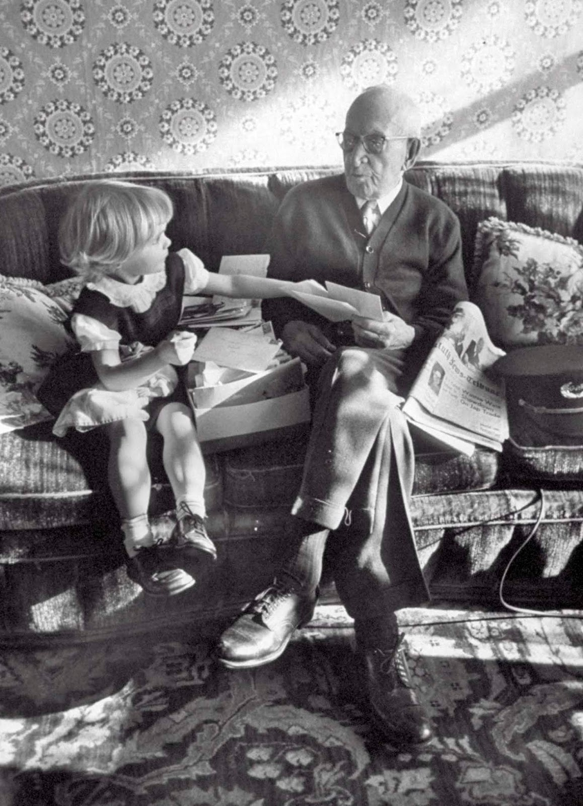 107 years old last remaining GAR Civil War Veteran Albert Woolson, relaxing on the couch while a little girl helps him sort through some mail. 1954.