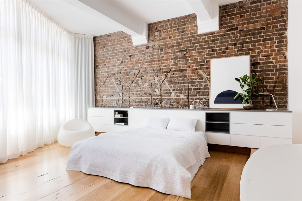 white-bedding-potted-plant-brick-accent-wall