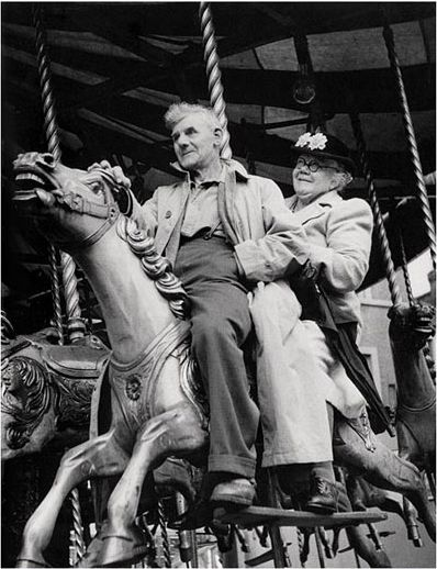 Beautiful black and white photo of an old couple riding a merry-go-round