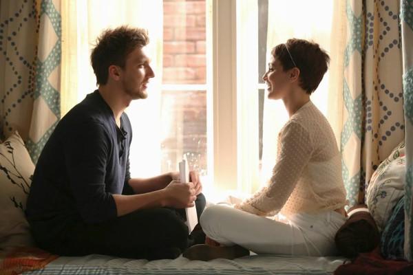 April e Leo conversam, sentados em frente a janela do quarto dela.