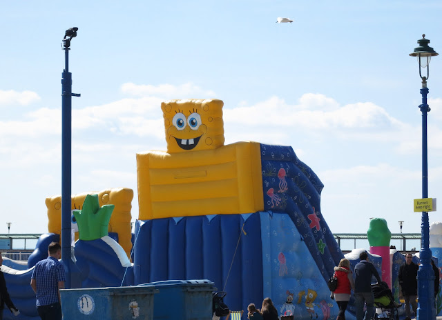 Gull flies over bouncy castle with face and teeth. ©Lucy Corrander.