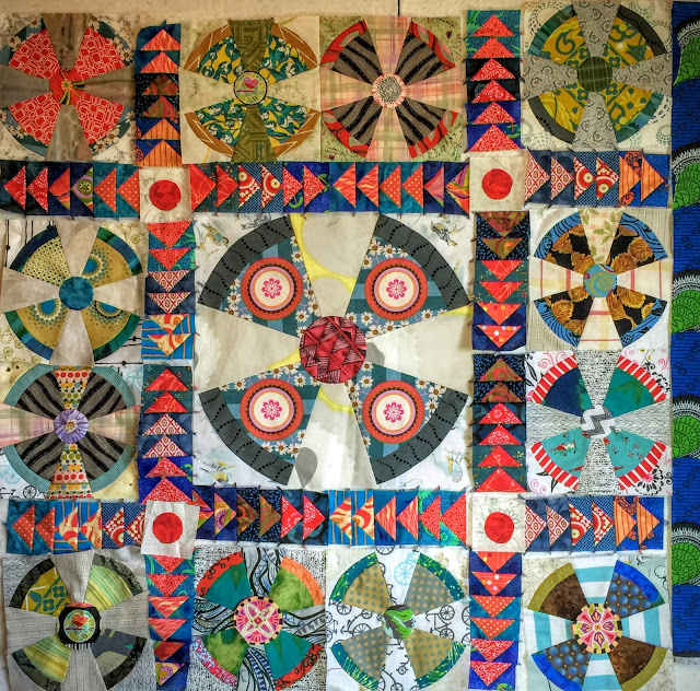 Propeller baby quilt with flying geese sashing and red circle posts