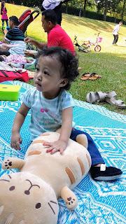 gambar kanak-kanak perempuan 1 tahun duduk atas tikar di taman
