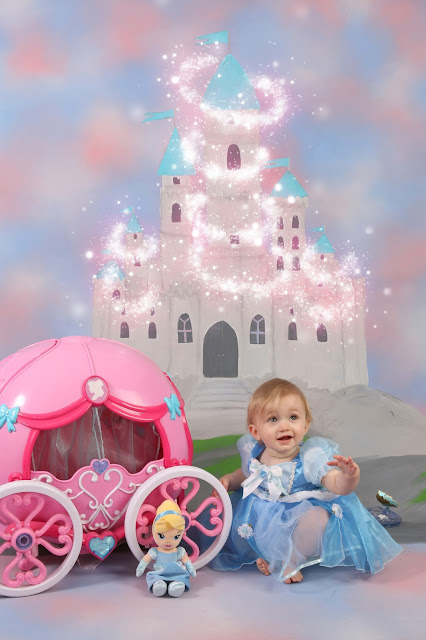 Baby girl at Disney themed photoshoot with Cinderella style background dress and props