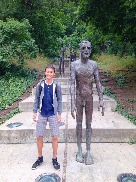 boy standing beside a statue