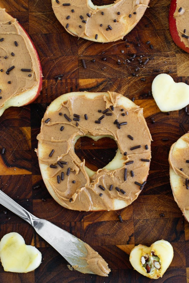 """Sliced Apple """"Donuts"""" are a fun and healthy play on yeast doughnuts, but instead of dough, they're made with sliced apples, peanut butter for frosting, and a sprinkle of chocolate jimmies."""