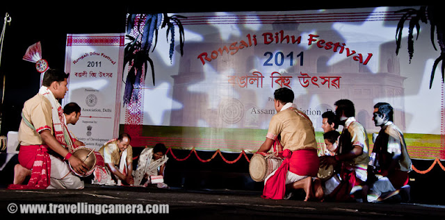Huchori Performance by an Assamese group of boys @ Rongali Bihu Festival, IGNCA, Delhi : Posted by VJ SHARMA on www.travellingcamera.com : Huchori - Huchori is an integral part of Rongali Bihu. Choral parties of singers and dancers moving from house to house is a salient feature of Rongali Bihu !!!Huchori is a regular thing which happens during the Rongali Bihu and it is a custom of community singing in which a group of singers visit each home in their locality and sing songs containing spiritual and moral values. The group comprises only of men and the event coincides with the Assamese New Year. The group visits every house irrespective of caste, creed and social status of the householder. During the reign of the Ahom dynasty, Huchori singing was a usual custom in the royal palaces. At a later period it began to be practiced by common people.A group of boys performed Hichuri on the stage and it was really interesting to see overall getup of folks in the groups and it seems elder folks also join this group to better guide the younger ones :) .. Although I was not able to make any sense out of the songs or dialogs, but it looked very interesting !!!Huchori group begins its procession from the village headman's house and continue towards the other houses in the vicinity. The procession proceeds amidst chanting, singing and dancing. Visiting each house in the village, the group accepts some donation from the residents. The singers usually carry a staff, a bag, an umbrella and a lamp while roaming around the village. Their instruments comprise of dhol (drum), taal (cymbals), pepa (horn pipe) and taka (bamboo clapper).This seems more like Lohri in North India.. Specially in Punjab and Himachal Pradesh !!! On Lohri week, boys make some groups and start visiting various houses in the village/town and sing different Lohri Songs... After that every house master offer some stuff like wheat, corns or rice.. and now people prefer to give money.. as it's convenient for both parties :)Huchori Performance at Rongali Bihu Festival in Indira Gandhi National Center of Arts was amazing and the energy level of folks performing was commendable !!!Here is one of the most enthusiatic performer of Hichori Dance who was handling dhol during Riganli Bihu in Delhi !!!Notice the dressed of all these folks and they have taken proper care of clothings they should use !!!Although I was not able to make out anything as they were singing in Assamese but their expressions were telling a story !! Here a couple is presenting something for god and praying for good !This whole event was organized by Assam association Delhi in partnership with Indira gandhi National Center of Art and it was wonderful experience at Rongali bihu festival !!!