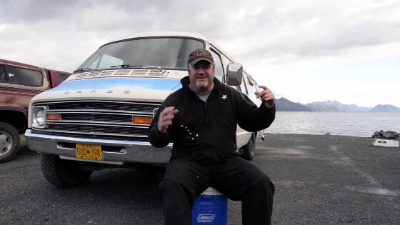 Smiling man sits on cooler in front of van by the Alaska sea shore. Is he homeless or not? You can't tell.