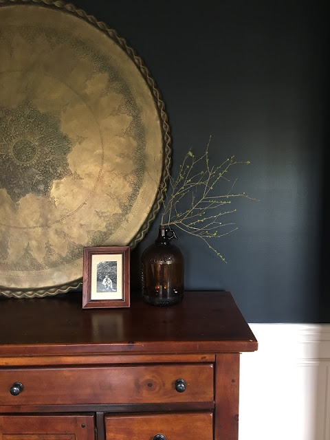 navy blue dining room with vintage brass details