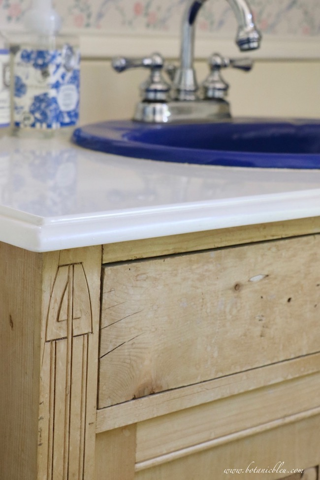 Budget wise cultured marble countertop with ogee edges and a blue porcelain sink in a vintage pine washstand