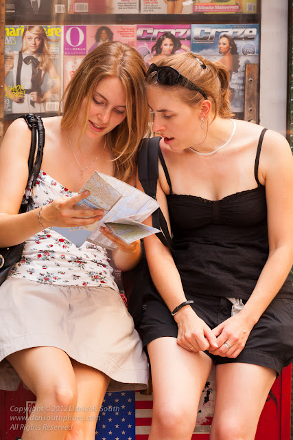 a photo of blonde female tourists reading a map in new york city