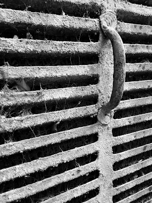 A black and white Minimalist Photo of the handle of a metal air cooler shot by Samsung Galaxy S6 Mobile Phone