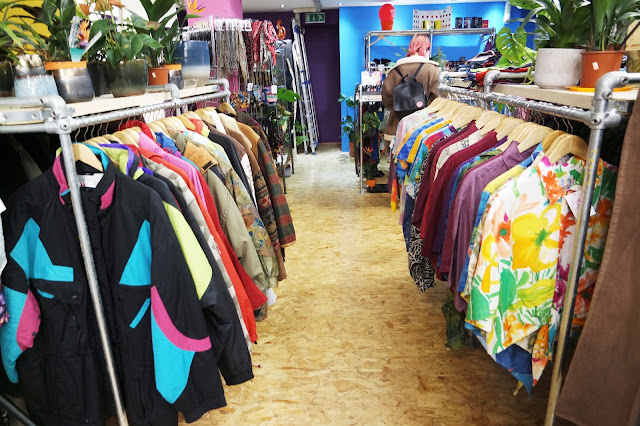 a photograph taken standing in the aisle of a clothing shop. The rack to the right has bright, tropical print shirts, and the left rack is hung with coats, including a black raincoat with pink and aqua patches.