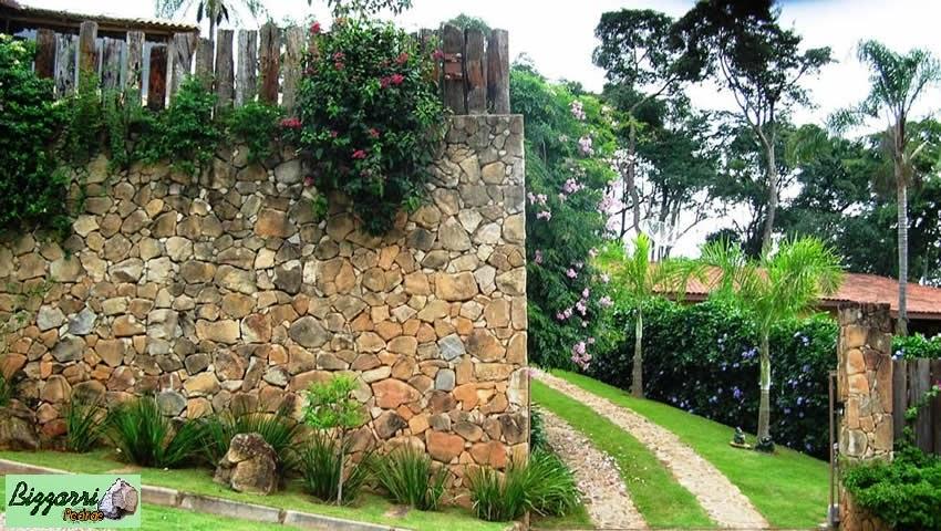 Detalhe do muro de pedra moledo com os caminhos de pedra e a execução do paisagismo.
