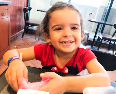 Young girl smiles with yogurt around her mouth