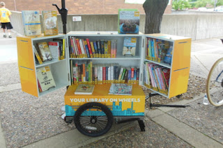 Book cabinet atop bicycle trailer, open to display cabinet shelves filled with books