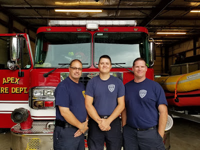 3 firemen in front of fire truck