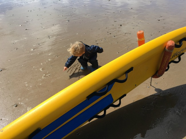 Ogmore-by-sea-a-toddler-explores-toddler-on-beach-near-lifeguards-surfboard