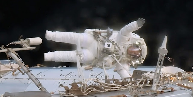Astronaut Jack Fischer waves while attached to the Destiny laboratory during a spacewalk to replace a failed data relay box and install a pair wireless antennas. Credit: NASA
