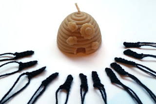 Twelve black rectangular shapes in a semi circle. A beeswax candle in the shape of a beehive is in the centre of the circle.  Yarn threads lead away from the centre.