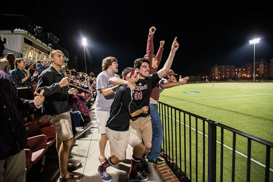 Guys cheer at a random men's soccer game.