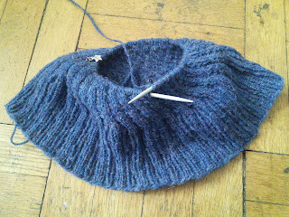 An incomplete hat made of blue yarn, with live stitches on a circular needle.  The hat is being knit from the brim up, with a ribbed brim and a spiraling cable pattern.