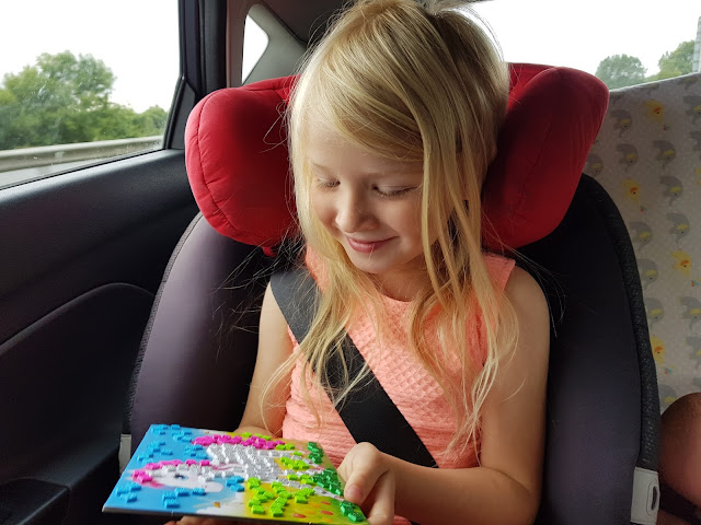 A young girl in a car seat in a car looking at a completed pony mosaic