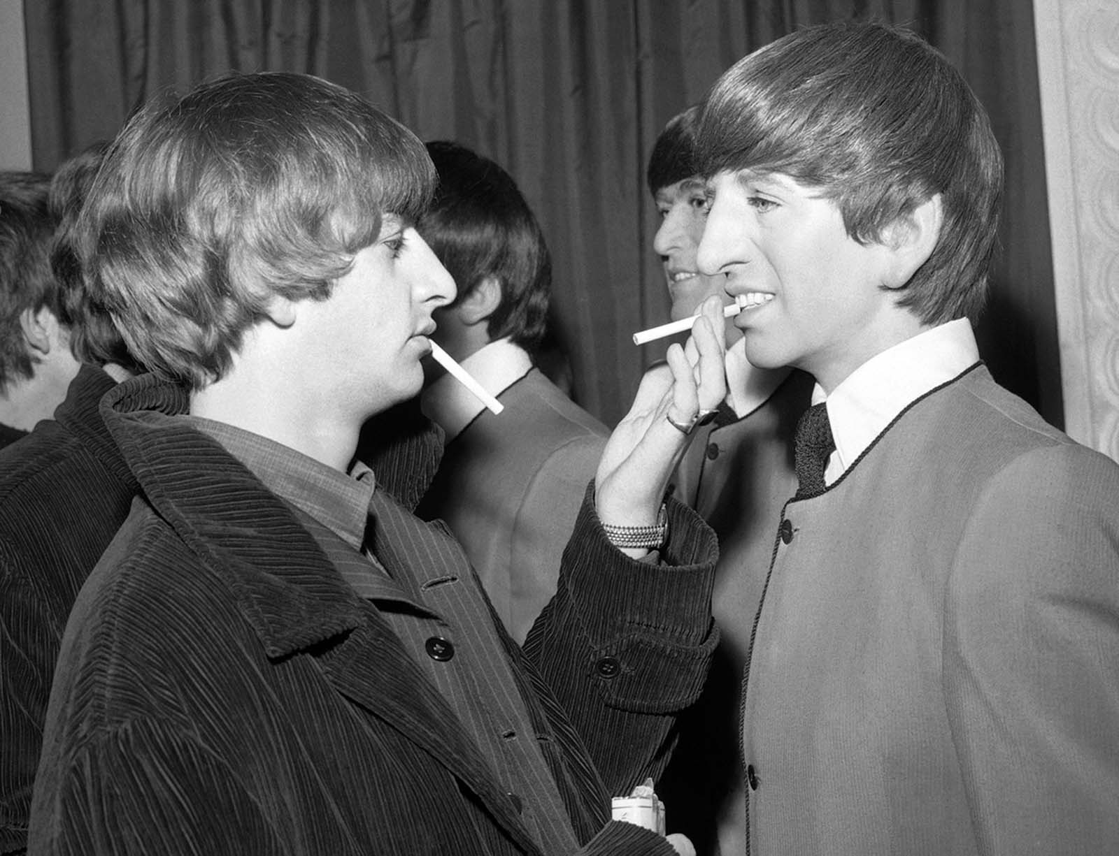 Beatle drummer Ringo Starr eases the pain on a wax likeness of himself with a cigarette, during the unveiling ceremony for four wax models of the Beatles at Madame Tussaud's Waxworks, in London, England, on April 29, 1964.