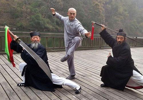 El monje practiva kung-fu en china junto a dos ancianos maestros.