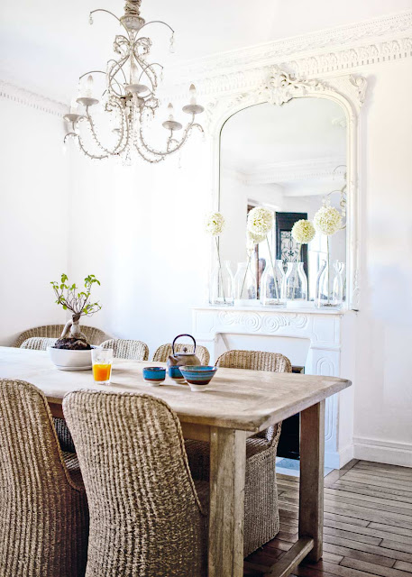 Dining room with wicker chairs wood farmhouse table, large traditional mirror on the fireplace mantel, a white fireplace and a chandelier