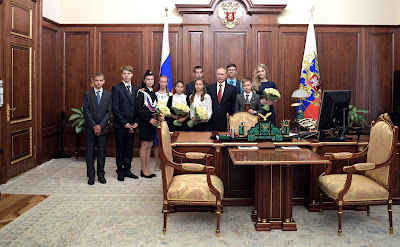 President Vladimir Putin with Russian children in his office.