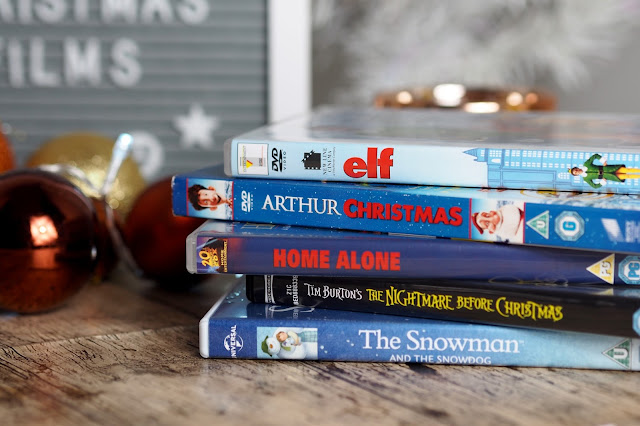 pile of DVDs, the snowman and the snowdog at the bottom, on top is the nightmare before christmas, on top of that is home alone, then arthur christmas and at the top is elf