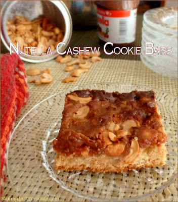 Nutella Cashew Cookie Bars start with a cookie crust, have a cashew center and are baked topped with a gooey Nutella mix. | Recipe developed by www.BakingInATornado.com | #bake #dessert