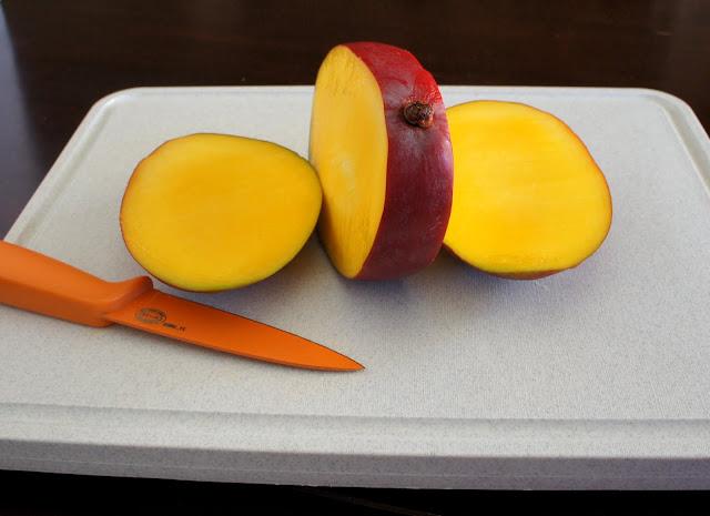 A sliced mango on a cutting board