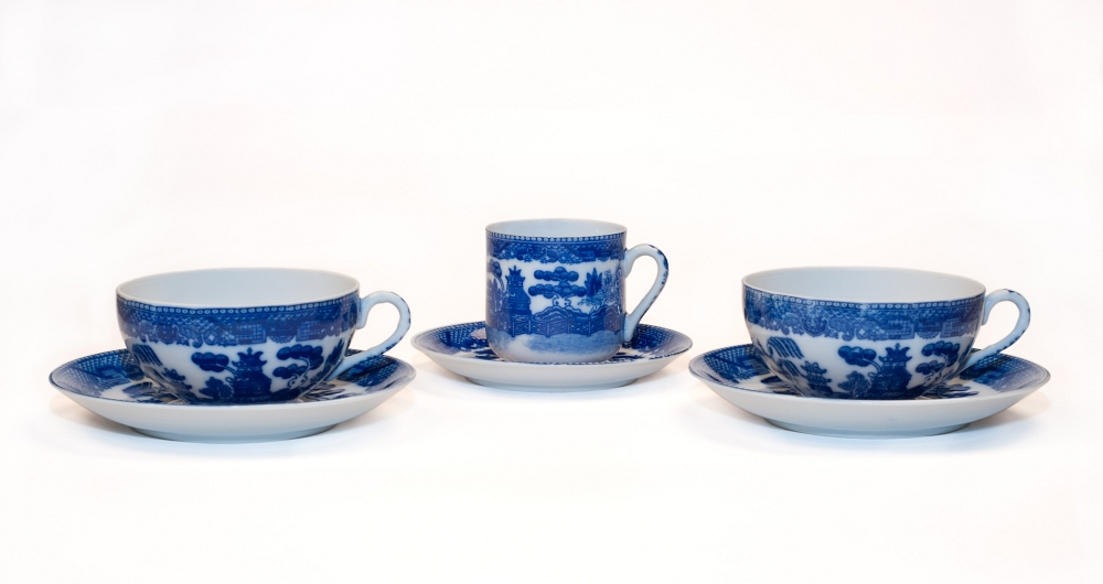 Three blue willow tea cups of fine bone china; the one in the middle is a demi-tasse cup.