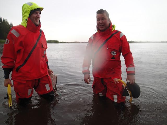 Kaksi pelastautumispukuista miestä rantavedessä