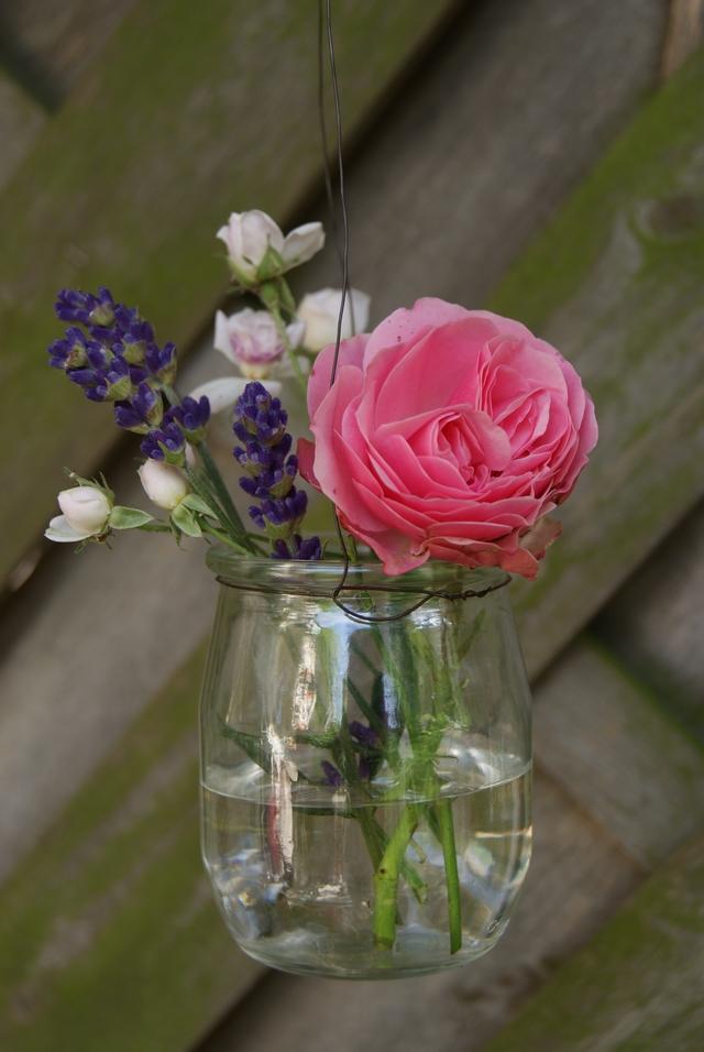 Hängende Glasvase mit Rosen und Lavendelblüten