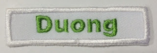 Name badge with green name embroidery