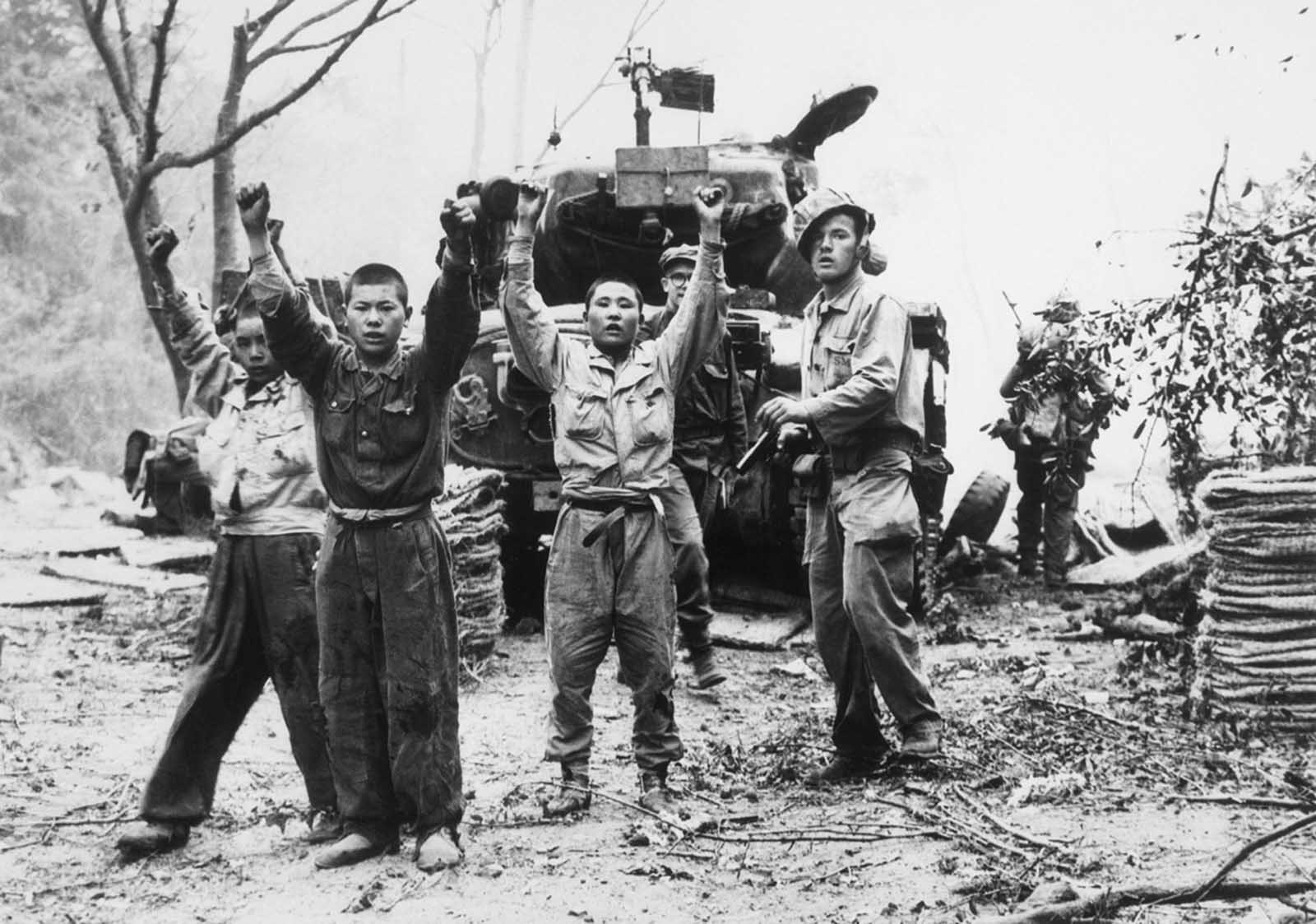 A U.S. Marine (right) orders captured North Koreans to keep their hands up on September 20, 1950. In the background is one of the tanks which came ashore in the assault at Inchon.