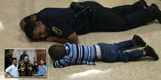 a policeman lying on the floor with a young boy