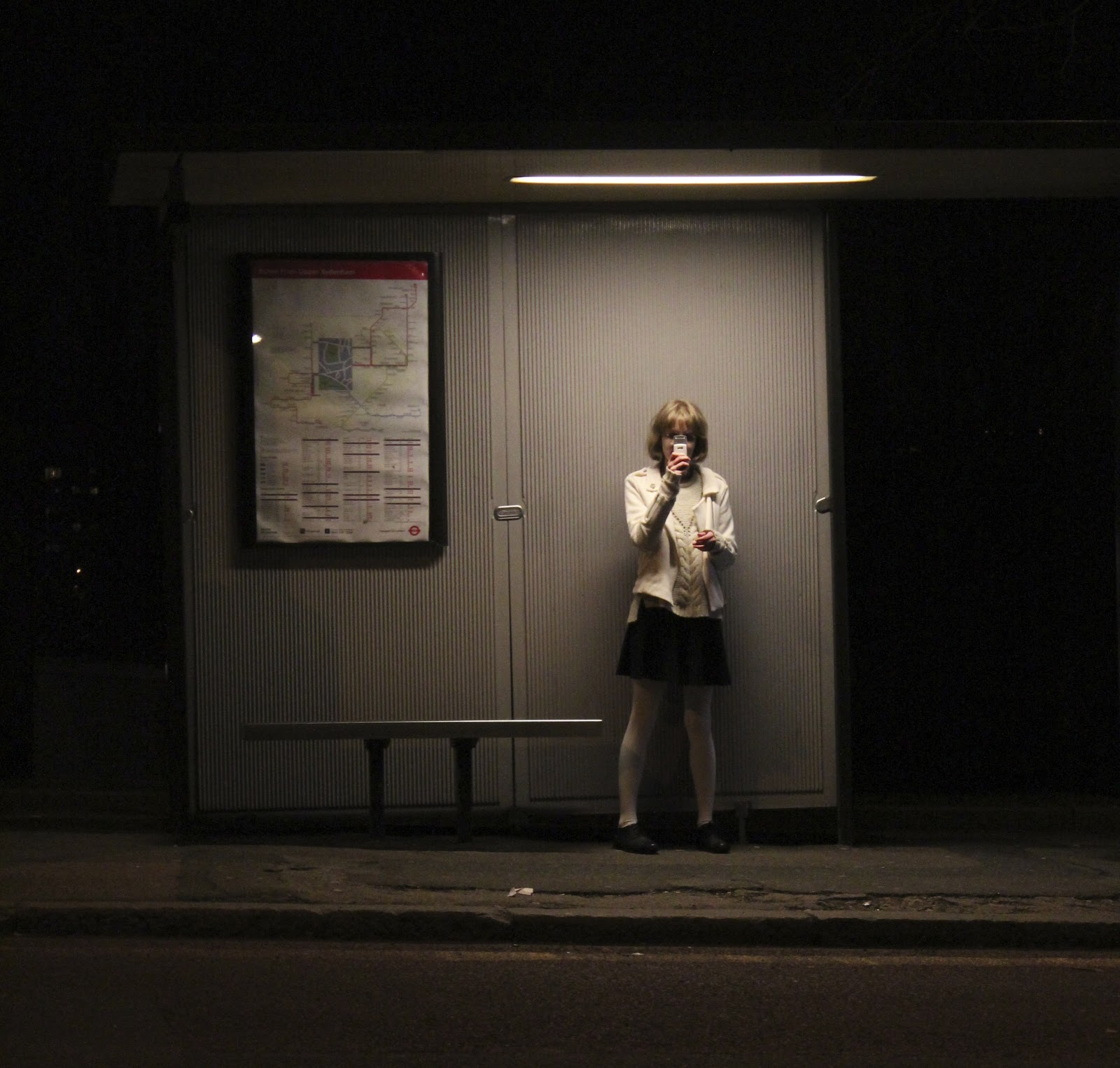 A woman is standing at a bus stop. She has her phone in front of her face to take a picture with it.